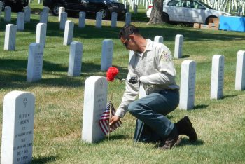 Lyons placing flags, flowers at grave.