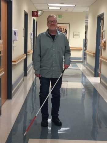 A male Veteran walks down a hall with a cane