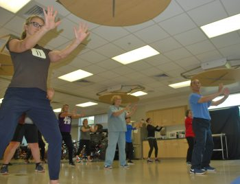 VA workers and patients in tai chi, mid pose.