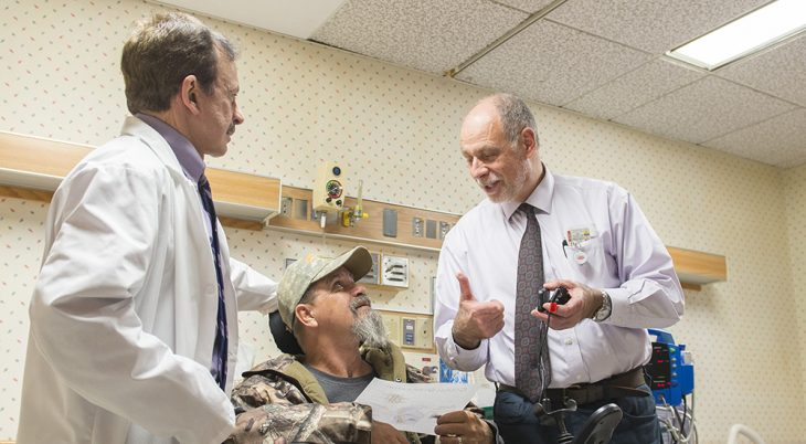 Two doctors and a Veteran patient in a wheelchair
