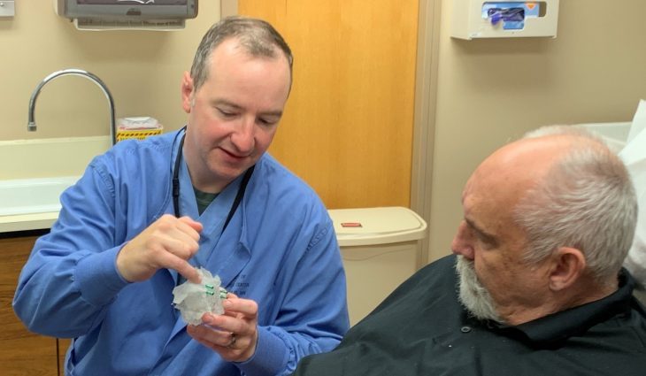 A dentist shows a male patient a 3D model of his planned surgery
