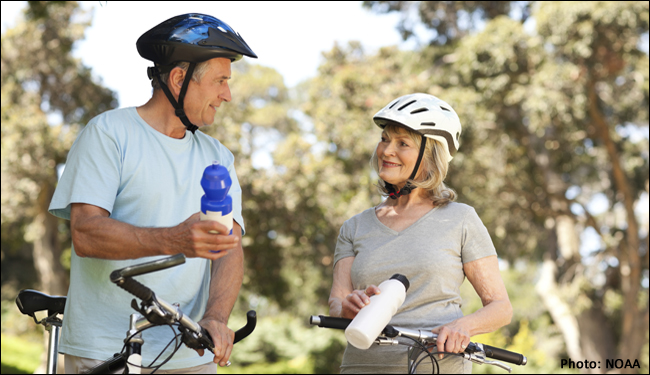Man and woman on bikes drinking water