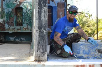 Frankie Perez, Army veteran and Puerto Rico 1st Service Platoon Leader, repaints an area of the old Miami Zoo during a service project.