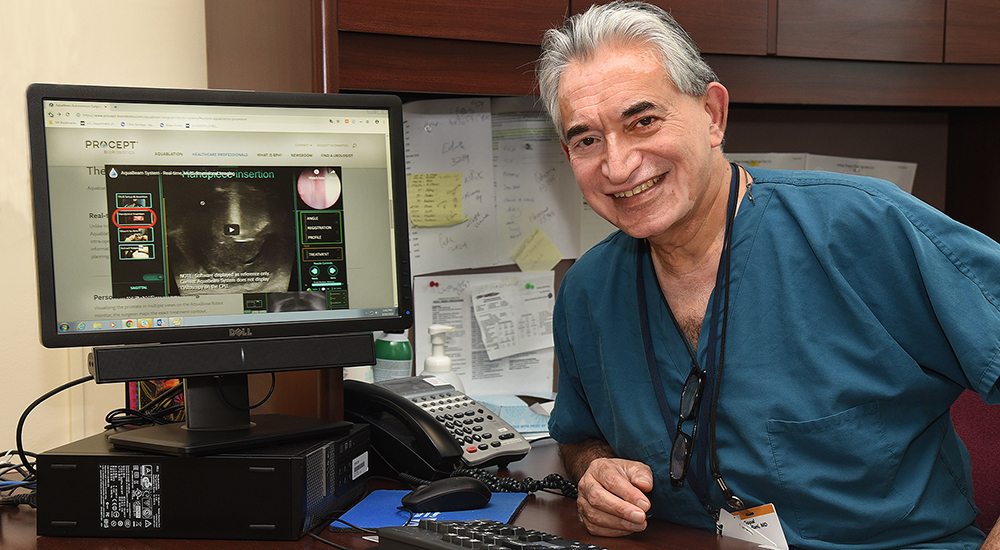 A male physician at his desk next to a computer monitor