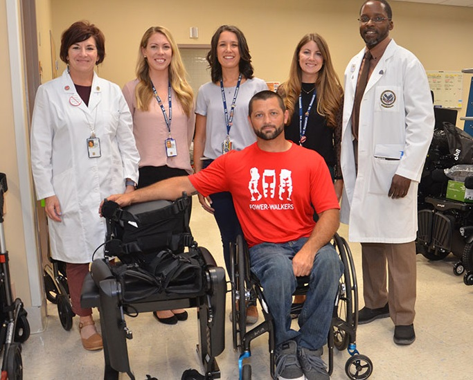 A man sitting in a wheelchair adjacent to the exoskeleton with five health care workers standing behind him