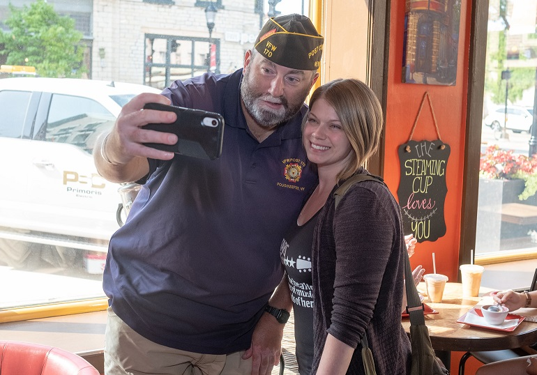 A man and a woman pose together for a selfie in a coffee shop