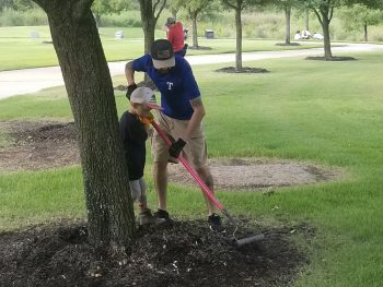A father and son spread mulch tree rings at the Dallas-Fort Worth National Cemetery Sept. 11, 2019.