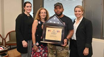 A male Veteran and three female VA clinicians with a flag certificate in a frame.