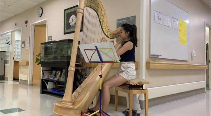 A young female musician volunteer plays a harp in a hospital hallway