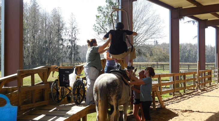 Four people help a Veteran onto a horse's back using adaptive equipment