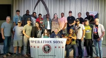"Twenty-one people stand on a stage holding a banner that reads ""Operation Song"""