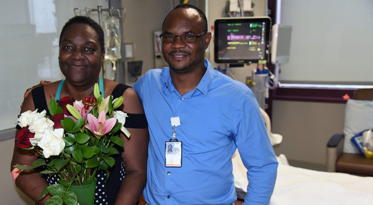 A woman accepts flowers from her VA nurse