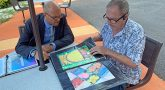 Two men sitting at an outdoor table looking at a portfolio of paintings