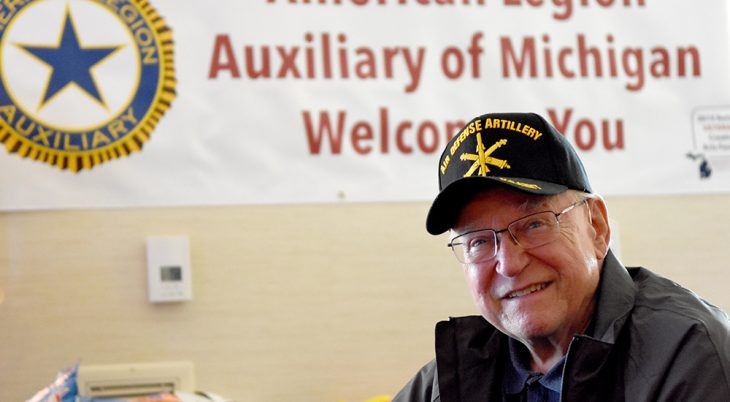 Man wearing an Air Defense Artillery cap sits in front of a banner that reads American Legion Auxiliary of Michigan Welcomes You at the National Veterans Creative Arts Festival