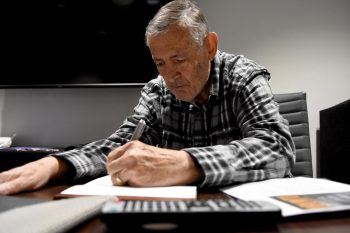 A Veteran writing at a table during the National Veterans Creative Arts Festival.