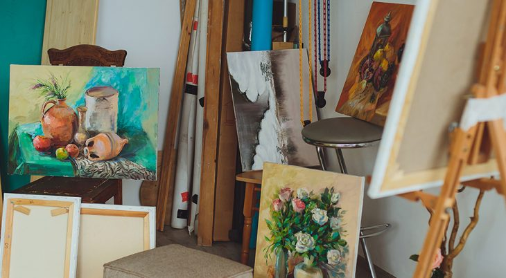 Several art paintings on easels and chairs in a room