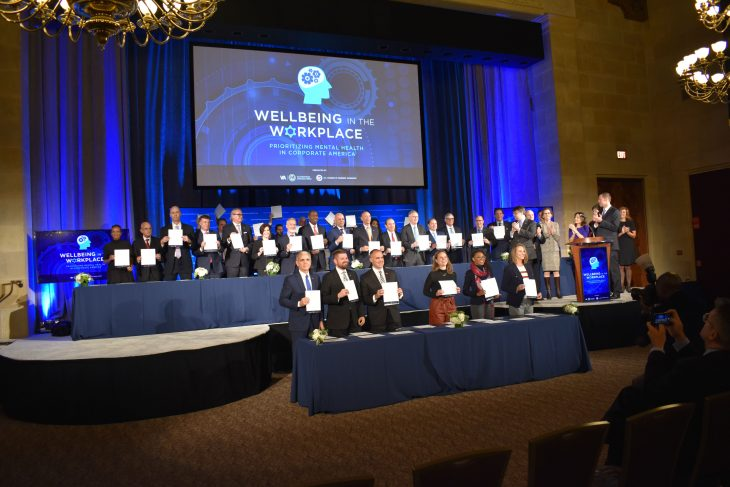 "Company representatives hold copies of their signed ""Pledge to Prioritize Mental Health and Emotional Wellbeing in the Workplace"" during a Nov. 13 event at the U.S. Chamber of Commerce in Washington, D.C."