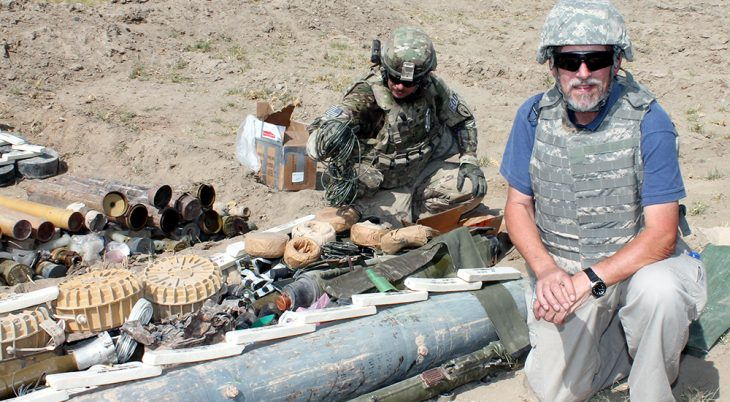 A man kneeling next to munitions in Afghanistan
