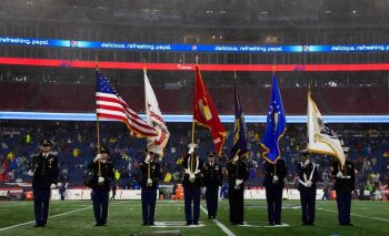 A joint color guard presents flags at the Nov. 24 Salute to Service game.