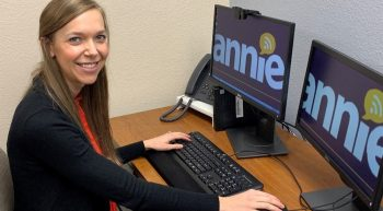 woman at computer with two monitors with the word Annie on each monitor