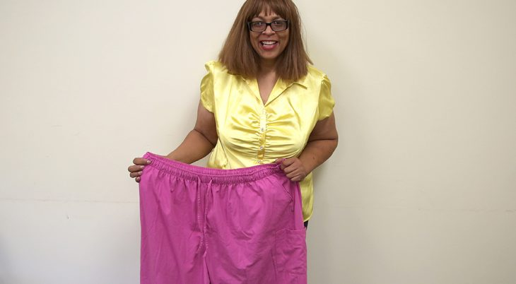 A woman holds up a large pair of pants