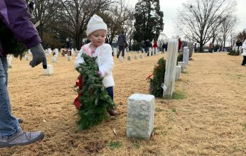A child places a wreath at Raleigh National Cemetery, North Carolina.