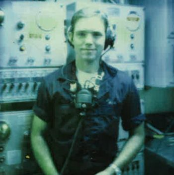 A young man wearing headphones in a ship's control room
