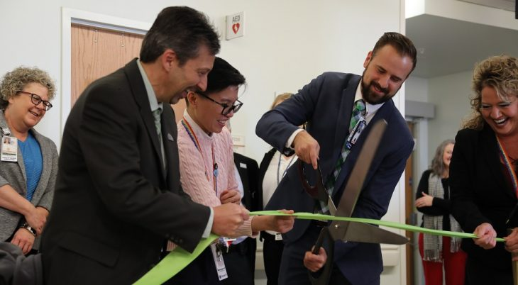 Three people cut a ribbon to open a gambling residential treatment center