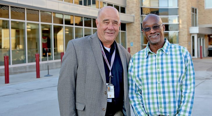 Two men standing in front of a VA hospital