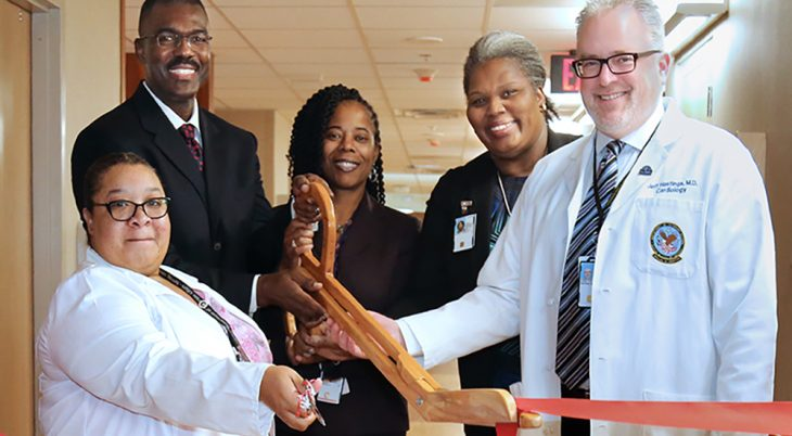 Group of people use large scissors to cut a ribbon opening a hospital wing