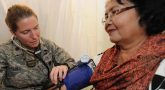 Female Army doctor takes the blood pressure to check a woman's heart health