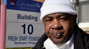 A man in a white watch cap stands in front of the Coatesville VA Medical Center