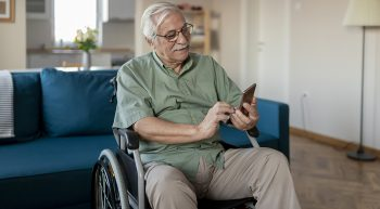 Handicapped senior person sitting in a wheelchair and using a smart phone at home in the living room