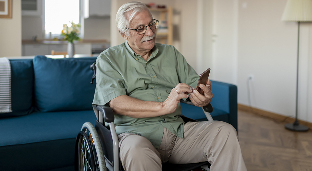 Picture of a Veteran in a wheel chair looking at his cell phone