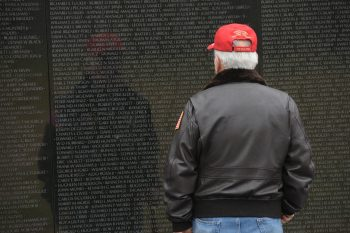 Vietnam Veteran stands in front of Vietnam Memorial Wall.