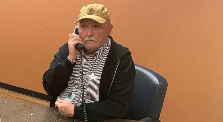 An older man at a desk in a lobby, speaking on the telephone