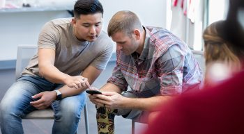 Two men, one with a prosthetic leg, discuss virtual health while looking at a cell phone
