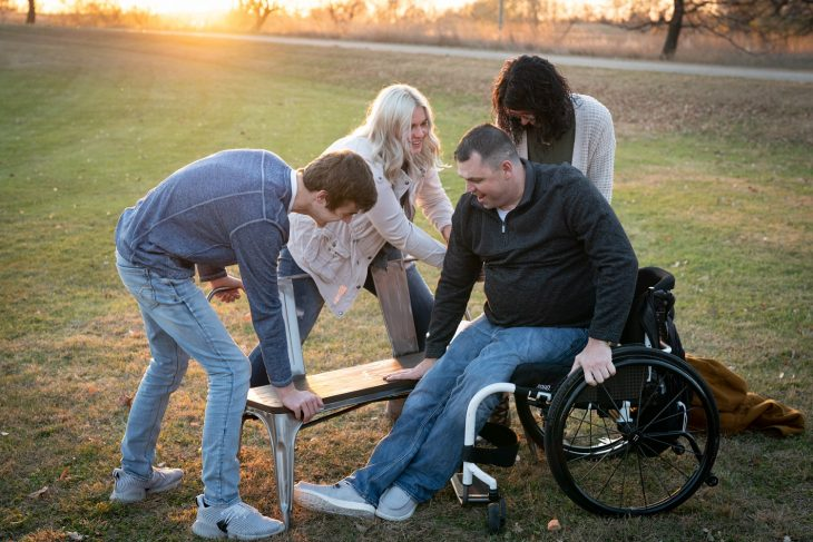 In preparation for a family photo, Army Veteran Jeff Edwards gets help from his girlfriend Dani, and kids Briona and Jakob, to transfer from his wheelchair to a bench.