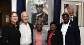 Five people pose in front of new painting of Marine Veteran