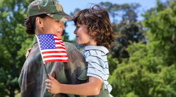 Woman soldier in uniform holds a boy who is holding an American flag