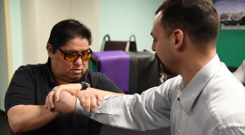 An instructor teaches a blind Veteran a self-defense move