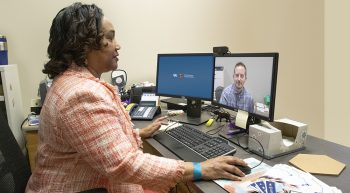 A woman conducts a virtual appointment with man on her computer screen