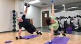 Man and women lift weights while doing push ups