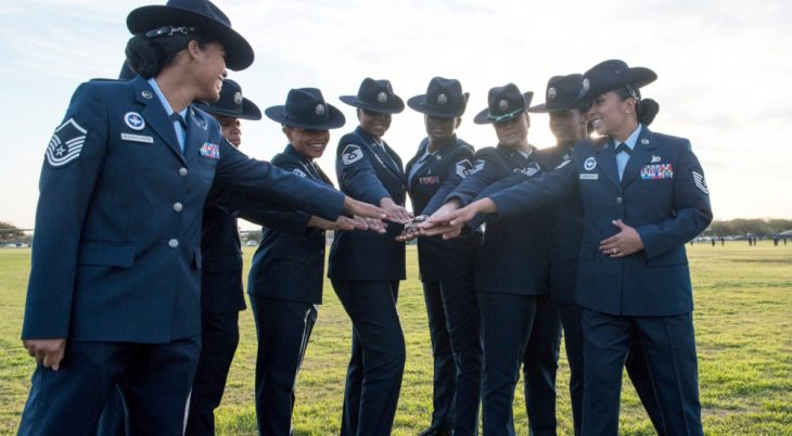 Group of Air Force women placing hands in a circle