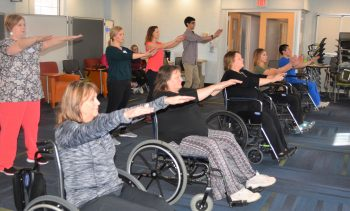 Ten people practice Tai Chi standing and sitting in wheelchairs