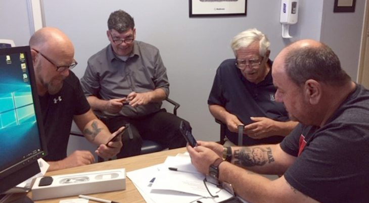 Four men looking at the Apple smart watches