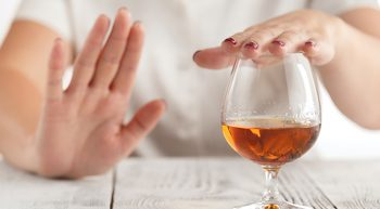 Woman saying no to a glass of alcohol