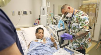 Man in hospital bed enjoys a virtual visit with family on computer tablet