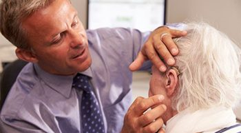 Doctor examining an elderly patient's ear
