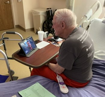 A Veteran patient at the Sioux Falls VA Community Living Center connects with family during a video chat with help from VA Chaplains.